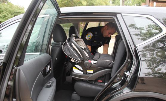 Officer installing a car seat into an SUV